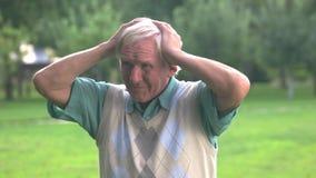 Ηλικιωμένο άτομο που κρατά το κεφάλι του απόθεμα βίντεο