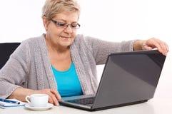 Ηλικιωμένο ανώτερο κλείνοντας lap-top γυναικών στον πίνακα στο σπίτι στοκ φωτογραφίες