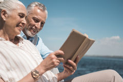 Ηλικιωμένο βιβλίο ανάγνωσης ζευγών στην αποβάθρα στην ημέρα Στοκ Φωτογραφίες