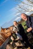 Ηλικιωμένο ζεύγος που ένα άλογο σε μια μάντρα Στοκ Εικόνες