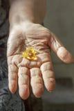 Ηλικιωμένο χέρι με το συμπλήρωμα Στοκ Εικόνες
