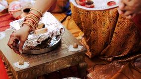 Η ινδή γυναίκα βάζει το ρύζι πέρα από τα καρύδια κατά τη διάρκεια της προ-γαμήλιας τελετής απόθεμα βίντεο