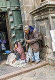 Η ινδική γυναίκα με το παιδί και ο λάμα θέτουν για τους τουρίστες σε Cuzco Στοκ Εικόνες