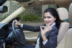 Η ινδική γυναίκα που οδηγεί ένα αυτοκίνητο και παρουσιάζει ΕΝΤΑΞΕΙ σημάδι Στοκ Εικόνες