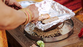 Η ινδική γυναίκα προετοιμάζει την πυρκαγιά στο κύπελλο κατά τη διάρκεια της προ-γαμήλιας ινδής τελετής φιλμ μικρού μήκους