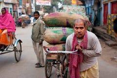 Η ινδική εργασία φορτωτών σκληρή και φέρνει τις τσάντες του φορτίου σε ένα παλαιό ποδήλατο Στοκ Εικόνα