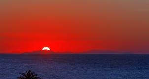 Ηλιοβασίλεμα ή ανατολή υποβάθρου φύσης πέρα από τις πέτρες βουνών και το νερό σύστασης θάλασσας Στοκ Φωτογραφία