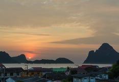 Ηλιοβασίλεμα ή ανατολή υποβάθρου φύσης πέρα από τις πέτρες βουνών και τη θάλασσα Στοκ Εικόνες