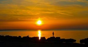 Ηλιοβασίλεμα από τη δύσκολη ακτή στο Κλίβελαντ Στοκ Εικόνες