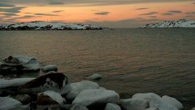 Ηλιοβασίλεμα, Βόρεια Θάλασσα, βράχοι στο χιόνι απόθεμα βίντεο