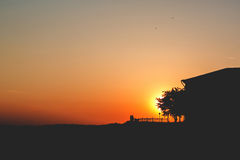 Ηλιοβασίλεμα Δύο άνθρωποι στέκονται σε έναν λόφο με ένα δέντρο και ένα ηλιοβασίλεμα σπιτιών Στοκ Εικόνες