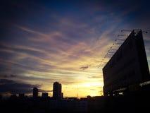 Ηλιοβασίλεμα εικονικής παράστασης πόλης σκιαγραφιών Στοκ Εικόνες