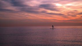 Ηλιοβασίλεμα εν πλω Άτομο στην ιστιοσανίδα στο ηλιοβασίλεμα υψηλό ηλιοβασίλεμα θάλασσας διάλυσης jpg κόκκινο ηλιοβασίλεμα τοπίων  απόθεμα βίντεο