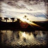 Ηλιοβασίλεμα επάνω από τα βουνά ερήμων με το νερό στην έρημο Καλιφόρνια ΗΠΑ φοινικών Στοκ Φωτογραφία