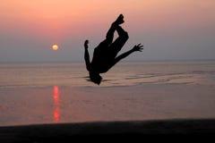 Ηλιοβασίλεμα και σκιαγραφία ενός χορευτή στην παραλία Στοκ Εικόνα