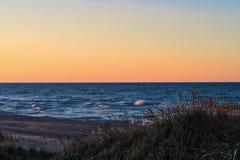Ηλιοβασίλεμα κατά μήκος της όμορφης παραλίας του Μίτσιγκαν λιμνών με την άποψη του ορίζοντα του Σικάγου στο μακρινό υπόβαθρο Στοκ εικόνα με δικαίωμα ελεύθερης χρήσης