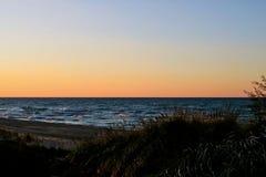 Ηλιοβασίλεμα κατά μήκος της όμορφης παραλίας του Μίτσιγκαν λιμνών με την άποψη του ορίζοντα του Σικάγου στο μακρινό υπόβαθρο Στοκ εικόνες με δικαίωμα ελεύθερης χρήσης