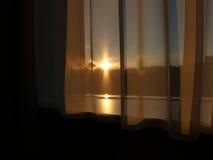 Ηλιοβασίλεμα μέσω των κουρτινών παραθύρων Στοκ Εικόνες