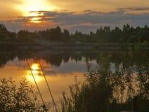 Ηλιοβασίλεμα με τα σύννεφα σε μια λίμνη Στοκ Εικόνα