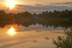 Ηλιοβασίλεμα με τα σύννεφα σε μια λίμνη Στοκ Εικόνες