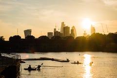 Ηλιοβασίλεμα πέρα από την πόλη του Λονδίνου με τα rowers στο πρώτο πλάνο Στοκ εικόνα με δικαίωμα ελεύθερης χρήσης