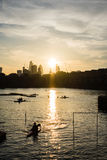 Ηλιοβασίλεμα πέρα από την πόλη του Λονδίνου με τα rowers στο πρώτο πλάνο Στοκ Εικόνες