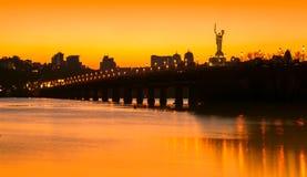 Ηλιοβασίλεμα πέρα από τη γέφυρα και τον ποταμό στην πόλη Στοκ Φωτογραφία