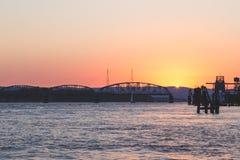 Ηλιοβασίλεμα πέρα από τη γέφυρα σε έναν κόλπο Στοκ Εικόνα