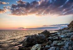 Ηλιοβασίλεμα πέρα από τη θάλασσα και τους βράχους Στοκ Φωτογραφία
