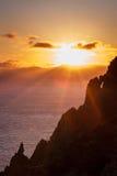 Ηλιοβασίλεμα πέρα από τη θάλασσα και το βράχο στο πρώτο πλάνο Στοκ Φωτογραφίες