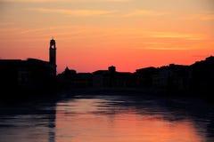 Ηλιοβασίλεμα πέρα από τη μαύρη σκιαγραφία του cityline της Πίζας και του ποταμού του Aron Στοκ Φωτογραφία