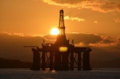 Ηλιοβασίλεμα πέρα από τις πλατφόρμες άντλησης πετρελαίου στο Cormarty Στοκ Εικόνα