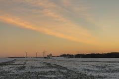 Ηλιοβασίλεμα πέρα από τον τομέα με τους ανεμοστροβίλους Στοκ Φωτογραφία