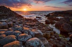 Ηλιοβασίλεμα πέρα από το γιγαντιαίο ` s βασαλτών υπερυψωμένο μονοπάτι στηλών, κομητεία Antrim, Βόρεια Ιρλανδία Στοκ Φωτογραφίες
