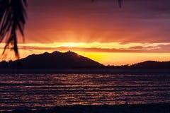 Ηλιοβασίλεμα πέρα από SanYa με το δέντρο καρύδων που πλαισιώνει το ηλιοβασίλεμα στοκ εικόνες