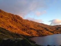 Ηλιοβασίλεμα πέρα από Scoat Tarn, Cumbria Στοκ Φωτογραφία