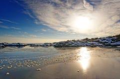 Ηλιοβασίλεμα πίσω από τα άσπρα σύννεφα πέρα από το φιορδ Στοκ Εικόνες
