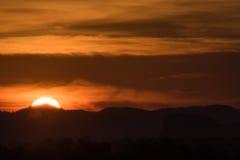 Ηλιοβασίλεμα πίσω από το βουνό και το σύννεφο Στοκ Φωτογραφίες