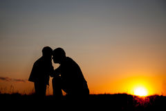 ηλιοβασίλεμα πατέρων και παιδιών, σκιαγραφία ενάντια στον ουρανό βραδιού στοκ φωτογραφία με δικαίωμα ελεύθερης χρήσης
