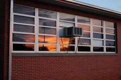 Ηλιοβασίλεμα που απεικονίζεται στην οικοδόμηση Στοκ Εικόνα