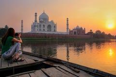 Ηλιοβασίλεμα προσοχής γυναικών πέρα από Taj Mahal από μια βάρκα, Agra, Ινδία στοκ φωτογραφίες