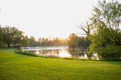 Ηλιοβασίλεμα σε ένα πάρκο πέρα από να φανεί μια λίμνη Στοκ φωτογραφία με δικαίωμα ελεύθερης χρήσης