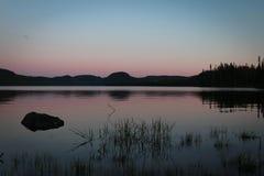 Ηλιοβασίλεμα σε μια ήρεμη λίμνη Στοκ Εικόνες