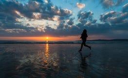 Ηλιοβασίλεμα σκιαγραφιών γυναικών jogger Στοκ Εικόνες