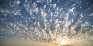 Ηλιοβασίλεμα στα χνουδωτά σύννεφα Στοκ Εικόνα