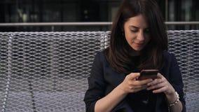 Ηλιοβασίλεμα στεγών της Μαδρίτης, γυναίκα με ένα smartphone, μπροστινή άποψη απόθεμα βίντεο