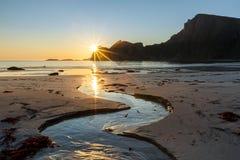 Ηλιοβασίλεμα στην αμμώδη παραλία με τον κολπίσκο στο πρώτο πλάνο Στοκ εικόνα με δικαίωμα ελεύθερης χρήσης