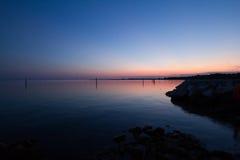 Ηλιοβασίλεμα στην αδριατική θάλασσα στην ακτή Sistiana με το ροζ και purpl Στοκ Φωτογραφίες