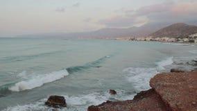 Ηλιοβασίλεμα στην παραλία με τις απόμακρες σκιαγραφίες βουνών απόθεμα βίντεο