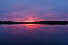 Ηλιοβασίλεμα στη λίμνη με την αντανάκλαση Στοκ Εικόνες